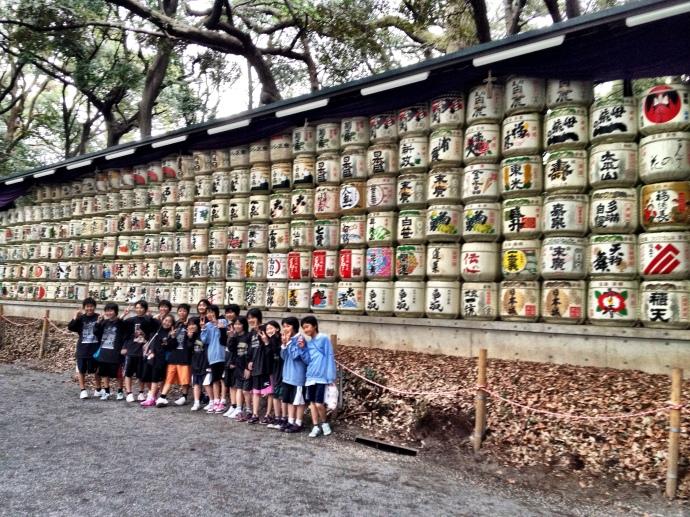 Japanese school children posing in front of donated sake casks at Meiji jingu shrine>