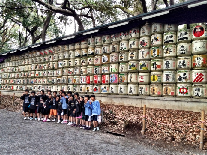 Japanese school children posing in front of donated sake casks at Meiji jingu shrine>