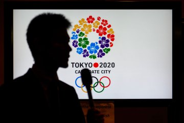 A journalist silhouette is seen during a press conference of Japanese Olympic medallists and former athletes to promote Tokyo for 2020 Olympic games on September 5, 2013 in Buenos Aires. Fears over radiation from the stricken Fukushima nuclear plant and fall-out from the bloody civil war in Syria are hanging over Tokyo and Istanbul's attempts to host the 2020 Olympics, amid suggestions that third candidate city Madrid could benefit.