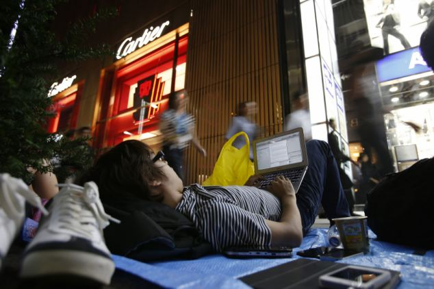 A man waits for the release of Apple's iPhone 5 near Apple Store Ginza in Tokyo